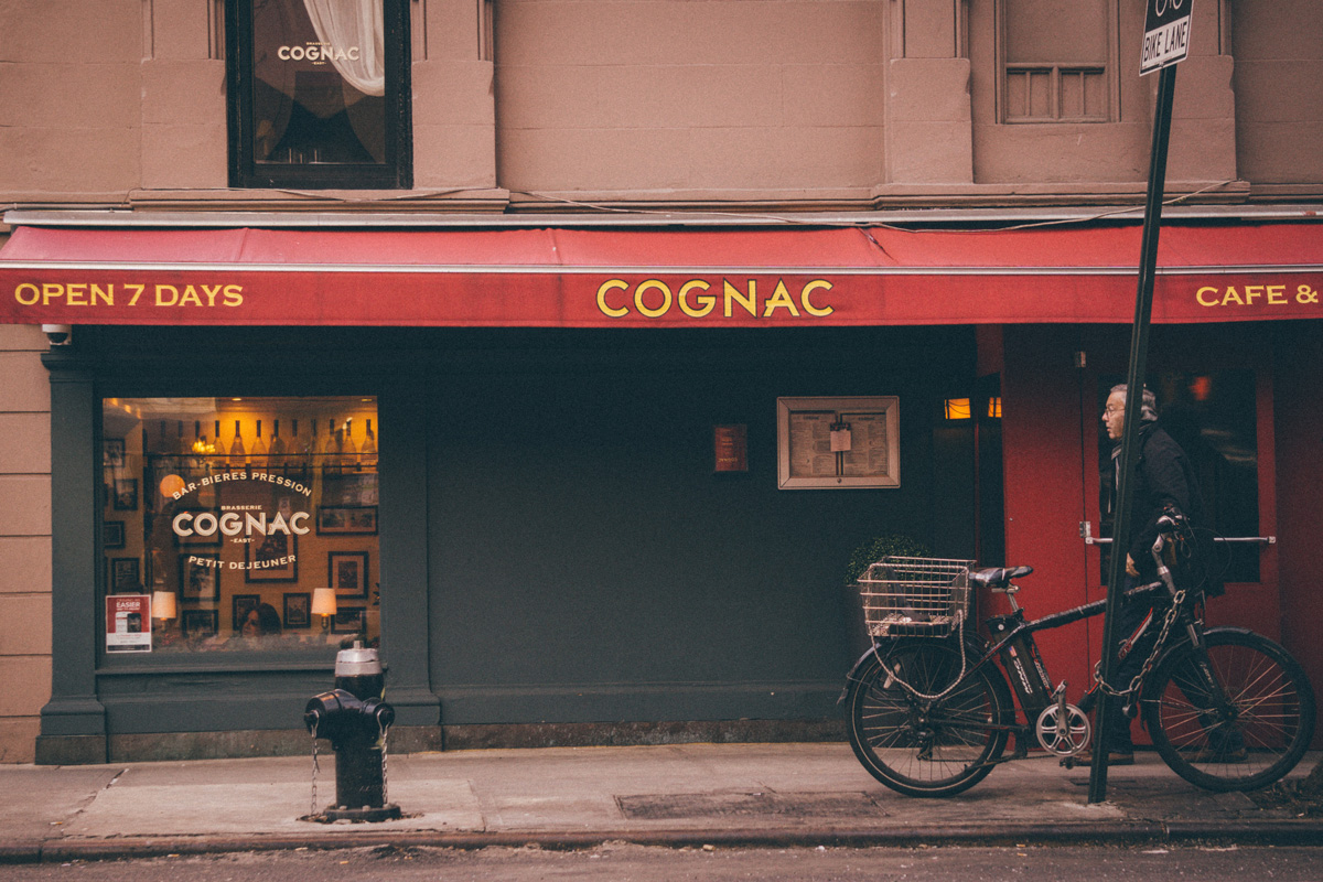 a man walks in front of a Cognac storefront